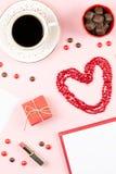 Tasse de café, bonbons, rouge à lèvres, forme de coeur et giftbox sur le fond rose Configuration d'appartement de concept de jour Images stock