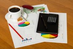 Tasse de café, calculatrice, stylo, bloc-notes, feuilles de papier avec l'a Images stock