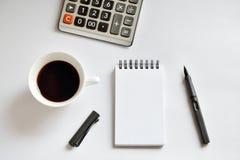 Tasse de café, carnet de notes à spirale, calculatrice, et stylo sur le backgr blanc Photo libre de droits