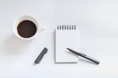 Tasse de café, carnet de notes à spirale et stylo sur le fond blanc Photo libre de droits