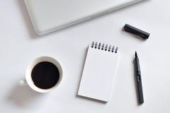 Tasse de café, carnet de notes à spirale, ordinateur portable, et stylo sur le fond blanc Photos libres de droits
