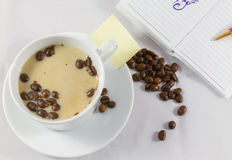 Tasse de café, carnet, stylo et grains de café sur le fond blanc Images libres de droits