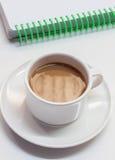 Tasse de café, carnet sur le fond blanc Photos stock