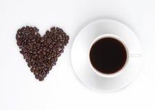 Tasse de café chaud avec la forme de coeur de haricots Images libres de droits