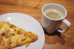 Tasse de café chaud avec la pizza délicieuse Photographie stock libre de droits