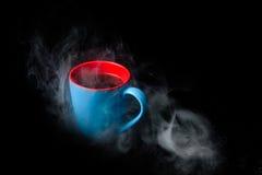 Tasse de café chaud entourée à l'arrière-plan de noir de vapeur Photo stock