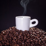 Tasse de café chaud sur des grains de café avec le fond noir Images libres de droits