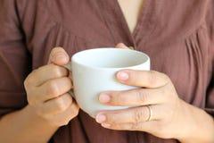Tasse de café chez la main de la femme Photographie stock libre de droits