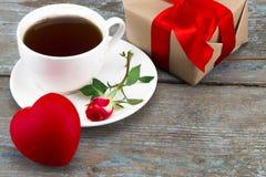 Tasse de café, coeur et rose de rouge avec le boîte-cadeau au-dessus du backg en bois Photos stock