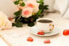 Tasse de café, coeurs de sucre et un bouquet des roses crèmes Image stock