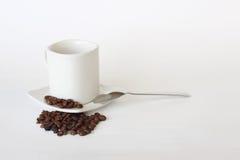 Tasse de café, cuillère avec du café renversé sur le blanc Images stock