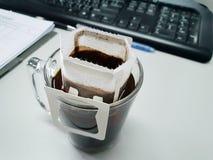 Tasse de café d'égouttement avec le clavier et le carnet Photos stock
