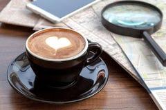 Tasse de café d'art de latte à coté avec le smartphone Photos stock