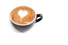 Tasse de café d'art de latte de forme de coeur sur le fond blanc d'isolement Images stock