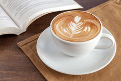 Tasse de café d'art de latte de rosetta sur la serviette avec un livre à coté image stock