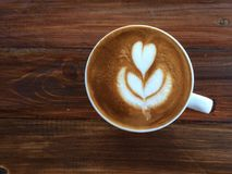 Tasse de café d'art de latte d'amour de coeur sur la table en bois Photographie stock libre de droits