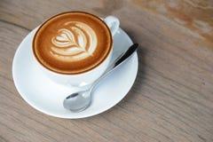 Tasse de café d'art de latte avec la forme de foyer pour la pause-café ou le petit déjeuner sur la table en bois images libres de droits
