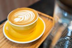 Tasse de café d'art de Latte en verre jaune de plat en bois Images libres de droits
