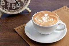 Tasse de café d'endroit d'art de latte de rosetta sur la serviette sur la table en bois Photographie stock libre de droits