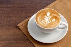 Tasse de café d'endroit d'art de latte de rosetta sur la serviette sur le fond en bois Photographie stock libre de droits