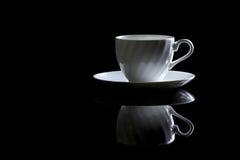Tasse de café dans le contre-jour sur un fond réfléchi noir Images libres de droits