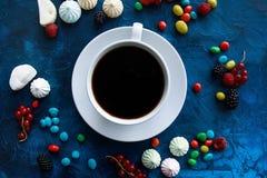 Tasse de café dans un cadre des baies, de la sucrerie et de la guimauve Photos stock