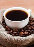 Tasse de café dans un sac des grains Images stock