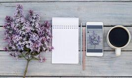 Tasse de café, de bloc-notes, d'une branche lilas et de téléphone avec le même lilas sur une table en bois blanche Images libres de droits