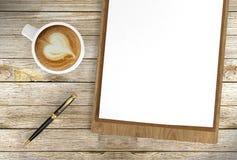 Tasse de café de cappuccino avec les papiers blancs sur le stylo bille de presse-papiers et, le café et le fond d'affaires photographie stock libre de droits
