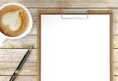 Tasse de café de cappuccino avec les papiers blancs sur le stylo bille de presse-papiers et, le café et le fond d'affaires photographie stock