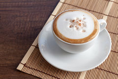 Tasse de café de cappuccino sur le tapis en bambou, sur l'esprit en bois de fond Photo stock