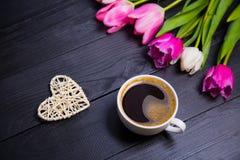 Tasse de café, de coeur en osier et de bouquet des tulipes sur le woode noir Photographie stock
