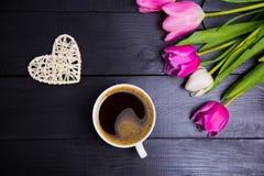 Tasse de café, de coeur en osier et de bouquet des tulipes sur le woode noir Photo libre de droits