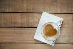 Tasse de café de forme de coeur sur le point table-sélectif en bois de foyer Photos stock