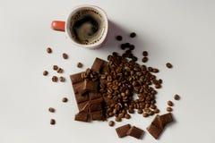 Tasse de café, de haricots café et de chocolat chauds sur la table blanche Photographie stock libre de droits