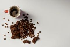 Tasse de café, de haricots café et de chocolat parfumés sur le fond blanc Image libre de droits