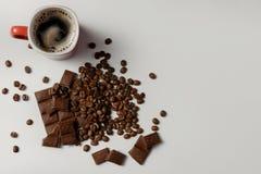 Tasse de café, de haricots café et de chocolat parfumés sur le fond blanc Image stock