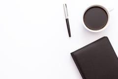 Tasse de café, de journal intime noir et d'un stylo sur un fond blanc Concept minimal d'affaires de lieu de travail dans le burea Photo libre de droits