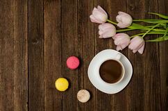 Tasse de café, de macarons et de tulipes roses sur le fond en bois Vue supérieure Photos stock