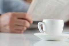Tasse de café de matin sur la table de travail avec des actualités de lecture d'homme d'affaires Photographie stock libre de droits
