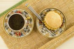 Tasse de café de porcelaine avec le motif et le gâteau de fleur Photographie stock libre de droits
