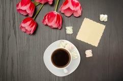 Tasse de café, de salutation propre, de guimauve et de tulipes roses Fond noir Vue supérieure Photo stock