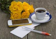 Tasse de café, de téléphone, de bouquet des roses et de carnet avec la poignée Photographie stock libre de droits