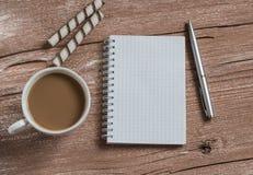 Tasse de café, des biscuits et d'un carnet ouvert vide sur une table en bois Vue supérieure Images stock