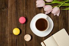 Tasse de café, des macarons, des tulipes roses et de carnet sur le fond en bois Vue supérieure Photos stock