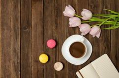 Tasse de café, des macarons, des tulipes roses et de carnet sur le fond en bois Vue supérieure Photographie stock