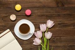 Tasse de café, des macarons, des tulipes roses et de carnet sur le fond en bois Vue supérieure Image stock