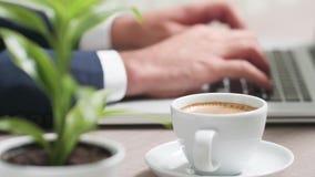 Tasse de café devant la dactylographie de mains d'homme d'affaires clips vidéos