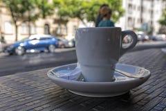 Tasse de café donnant sur la ville Fond brouillé Photographie stock