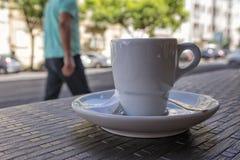 Tasse de café donnant sur la ville Fond brouillé Photos stock